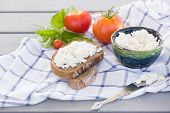 Organic Farming Cottage cheese in a green bowl slice of whole wheat bread with Homemade Ricotta cheese served with tomatoes and basil on wooden board on linen fabric. Healthy food concept poster