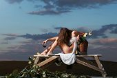 pretty girl in white sexy dress denuded gorgeous body with red wine glass wicker bottle and vine on evening nature over dramatic sky poster