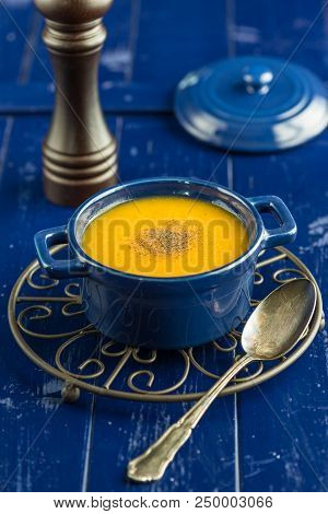 Carrot Soup In A Blue Pot On A Wooden Table Top