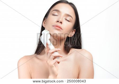 Young beautiful woman looks after skin with an exfoliating brush. Beauty portrait poster