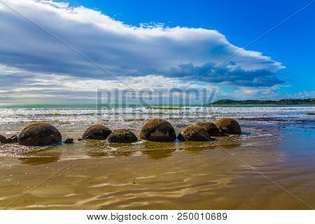 Boulders Moeraki - a group of large spherical boulders on the beach Koekokhe. Travel to New Zealand. Ocean evening tide. The concept of active, eco and photo tourism