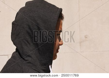 Sad Troubled Teenager School Boy With Hood On Posing Outdoor Standing Alone In Front Of Concrete Whi