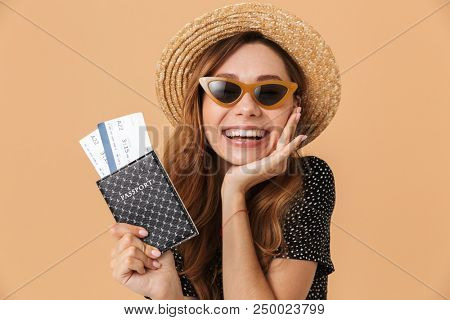 Charming brunette woman 20s wearing straw hat and sunglasses rejoicing while holding passport with travel tickets isolated over beige background poster
