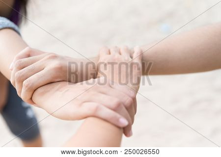 Three People Join Hands Together On White Sand Beach Background. Friendship Day, Collaboration Of Bu