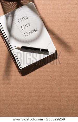 Top View Of Graphite Pencil And Textbook With Lettering Yes, No And Maybe On Cardboard