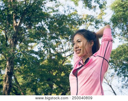 Asian Young Woman Warm Up The Body Stretching Before Morning Exercise And Yoga In The Park Under War