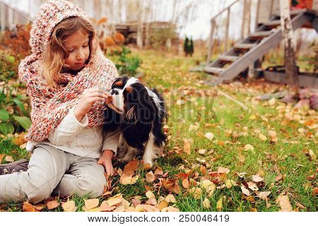 Happy Kid Girl Playing With Her Cavalier King Charles Spaniel Dog In Autumn, Walking Outdoor In Sunn