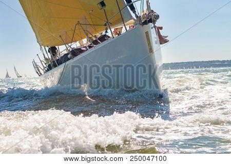 Close up of sailing boat, sail boat or yacht at sea with yellow sails