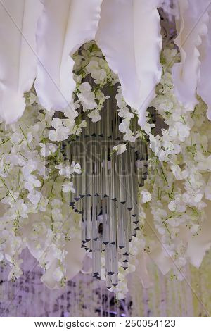 Chandelier And White Floral Decoration At The Wedding Banquet.