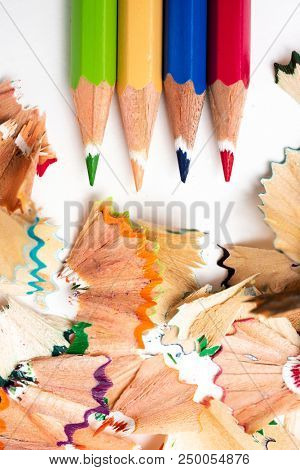 high angle view of some pencil crayons of different colors and a pile of fan-shaped shavings of different colors on a white background