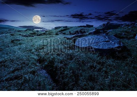 Cloud Over The Grassy Hillside With Rocks At Night In Full Moon Light. Path Uphill In To The Sky. Lo