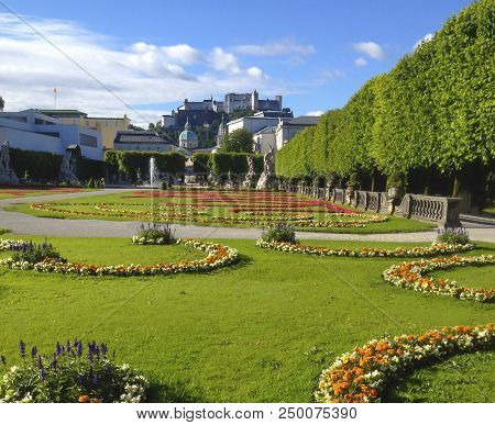 Beautiful Summer Day View Of Mirabell Gardens With Festung Hohensalzburg Castle In The Background, S
