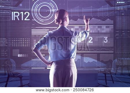 Clever Woman. Calm Attentive Young Programmer Standing Alone In Front Of A Futuristic Computer And C