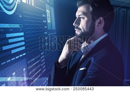Attentive Look. Calm Clever Programmer Wearing An Elegant Suit And Frowning While Thoughtfully Touch