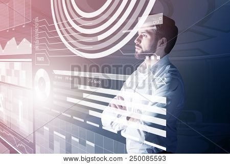 Thoughtful Person. Calm Attentive Web Developer Looking At The Transparent Screen While Standing Wit
