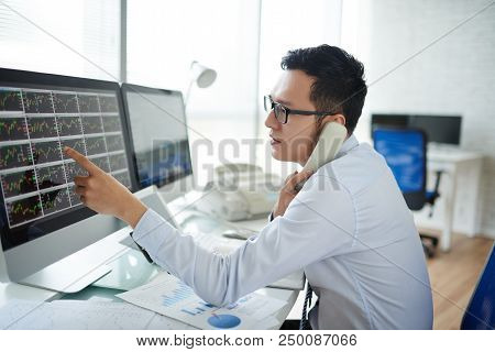 Young Vietnamese Stock Broker Discussing Stock Exchange Data On Computer Monitor With Colleague On P