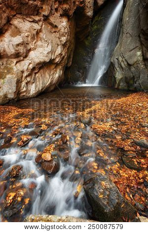 Beautiful River Waterfall In Autumn Forest, A Small Waterfall Part Of Fotinski Waterfalls, Rhodope M