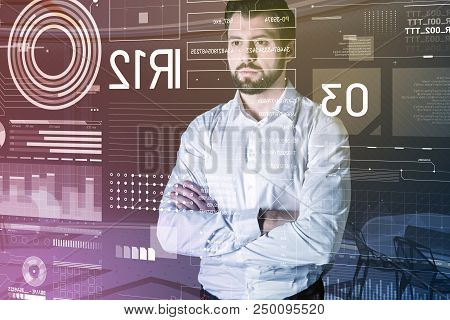 Serious Look. Clever Serious Programmer Feeling Worried And Standing With His Arms Crossed While Loo