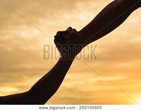 Closeup Helping Hands On The Sunset Sky Background. Rescue & Help Cencept