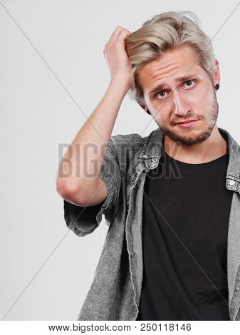 Confusion, Questionable. Standing Blonde Man Wearing Grey Shirt Being Confused And Scratching Head,