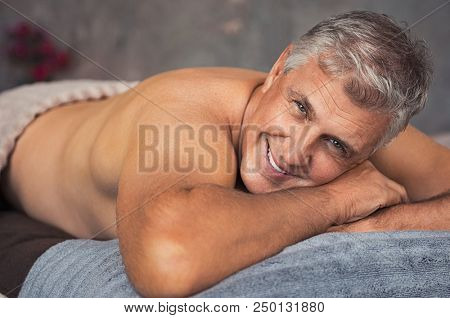 Smiling senior man lying on front on table spa and looking at camera. Retired man relaxing at wellness center. Portrait of mature man with grey hair waiting for massage treatment.