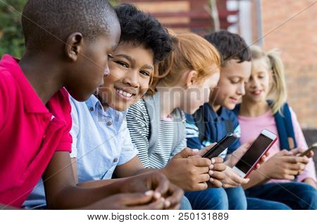 Portrait of smiling male child sitting in a row with other children while using cellphone outdoor. Cute pupils typing on mobile phone at school during recreation time. Kids holding smartphone.
