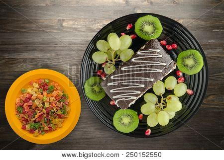 Dessert Of Cake And Fruit (grapes, Kiwi, Pomegranate) On A Wooden Background. Dessert On A Plate Top