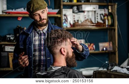 Man With Beard And Mustache In Hairdressers Chair, Shelves On Background. Hipster Client With Fresh
