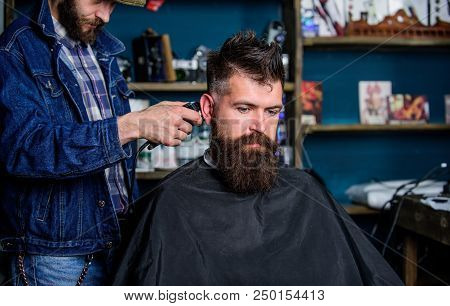 Barber With Hair Clipper Works On Hairstyle For Bearded Guy Barbershop Background. Hipster Client Ge