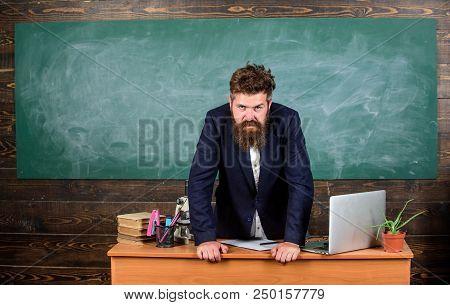 Teacher Strict Serious Bearded Man Lean On Table Chalkboard Background. Teacher Looks Threatening. S
