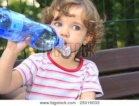 The little girl is drinking water from the plastic bottle.