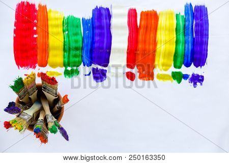 Art And Creativity Concept With Stripes Of Bright Vivid Paint In The Colors Of The Rainbow And A Jar