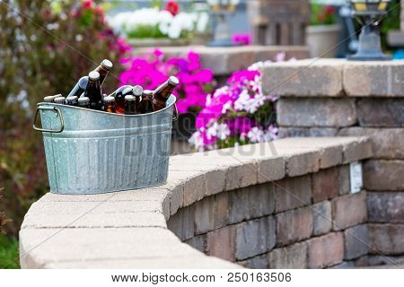 Galvanised Metal Tub Filled With Bottles Of Craft Beer Or Larger Chilling On A Curved Brick Patio Wa