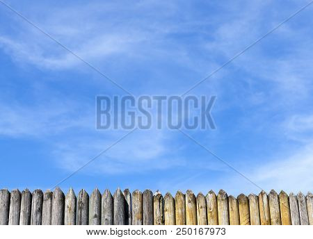 A Small Part Of The Sharp Stockade Made Of Pine Against The Blue Sky, The Landscape In The Spring