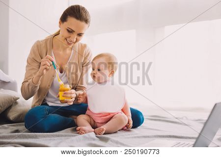 New Food. Cheerful Attentive Babysitter Smiling While Giving Tasty Fresh Baby Food To A Cute Toddler