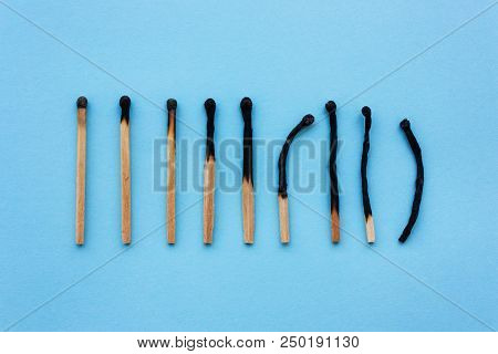Burned Matches In A Row On A Blue Background. The Concept Of Depression, Extinction, Illness, Burnou