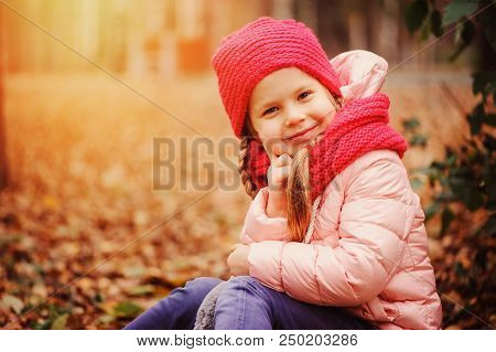 Autumn Outdoor Portrait Of Happy Little Child Girl Enjoying The Walk In Sunny Park In Warm Knitted H