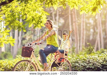 Happy Family. Smiling Mother And Son Riding Bike In The Park. Family Sport And Healthy Lifestyle