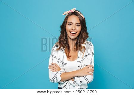 Photo of european brunette woman 20s wearing headband smiling and standing with arms crossed isolated over blue background