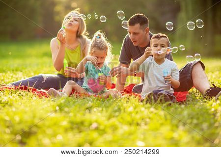 Young Happy Family With Children Blow Soap Bubbles Outdoor