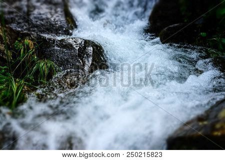 Close-up Streams Of Water Between Mountain Stones. Beautiful Mountain River Stream With Fast Flowing
