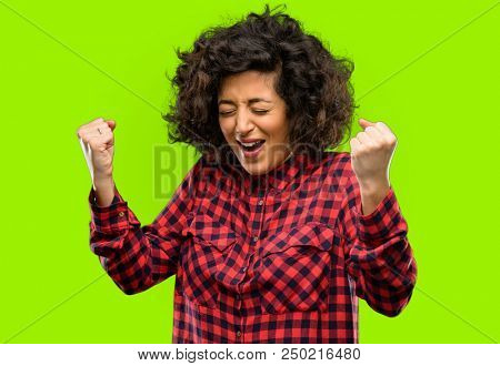 Beautiful arab woman happy and excited expressing winning gesture. Successful and celebrating victory, triumphant