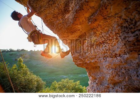 Picture Of Man Clambering Over Rock. Sunlight Effect