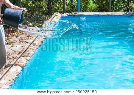 Man Pours Of Disinfectant From Bucket In Outdoor Swimming Pool On Backyard Of Country House