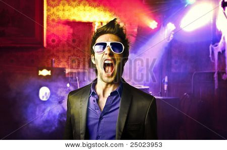 Young man screaming in a disco