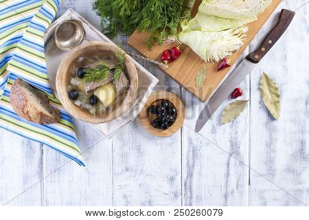 Traditional Soup Of Fresh Cabbage And Pulp Of Beef With Potatoes, In A Wooden Bowl On A White Backgr