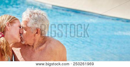 Verliebtes Senioren Paar beim Küssen im Hotel Pool im Urlaub