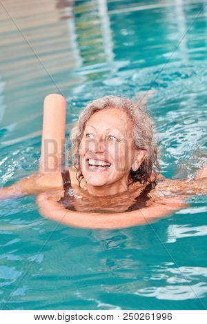 Vital senior woman is learning to swim with swimming noodle in the swimming pool