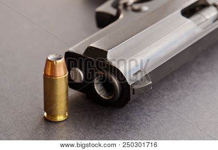A single 40 caliber hollow point bullet standing next to the muzzle of a black pistol on a black background poster
