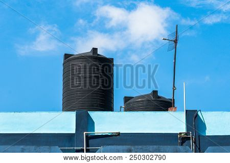 Water Tank On The Roof Over Blue Sky. Black Water Tank On The Roof Of A Tall Building Against A Blue